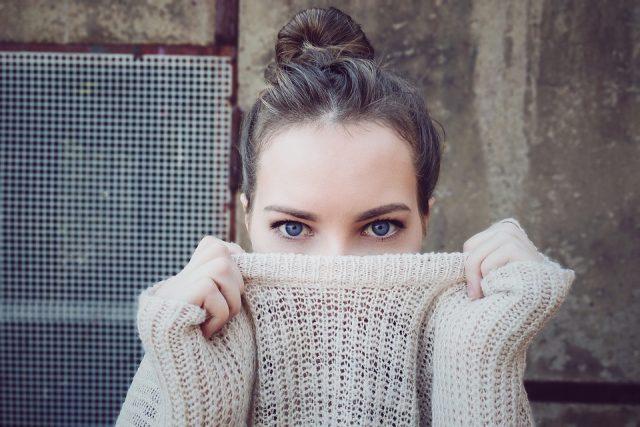タートルネックで顔を隠す女性