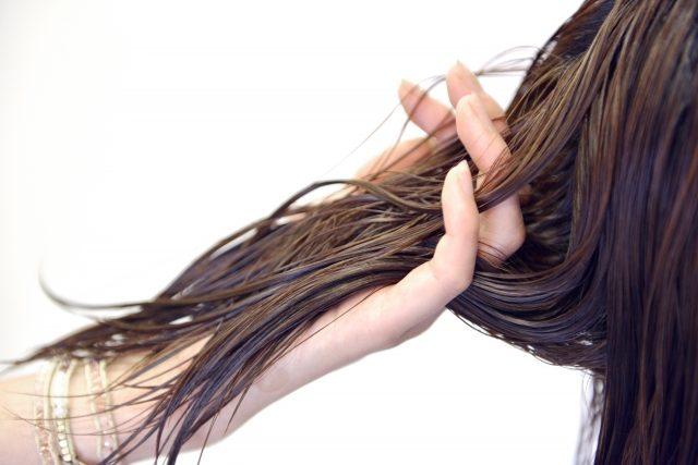 髪にトリートメントをする