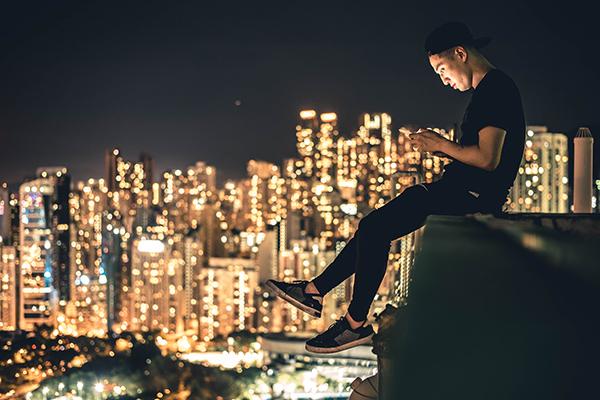 屋上でスマホを触る人