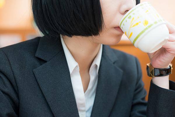 ファミレスでコーヒーを飲む女性