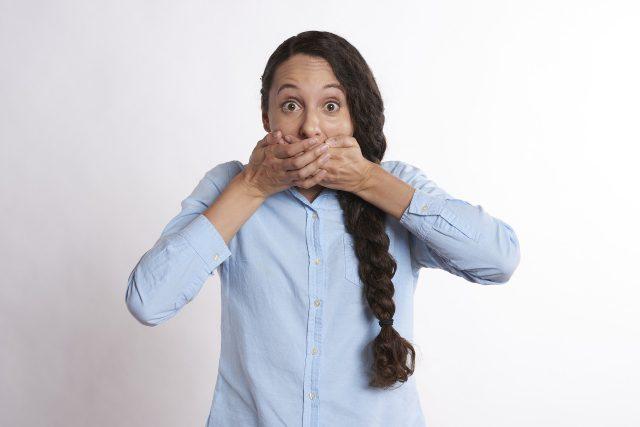 口を押える女性