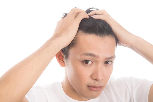 髪の毛をかき上げる男性