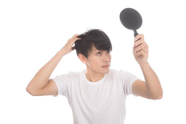 頭皮・髪の毛を確認する男性